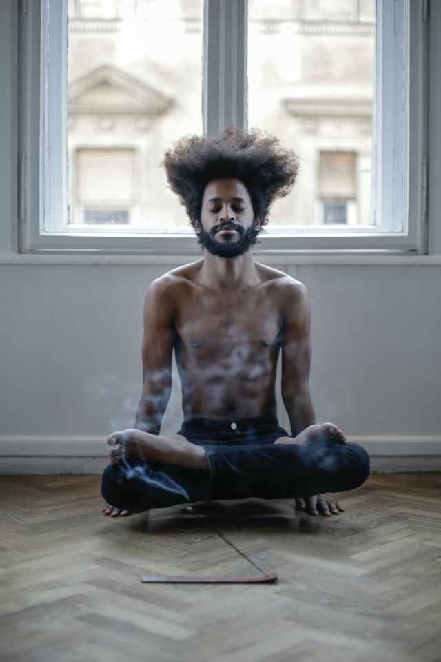topless man in black pants doing yoga
